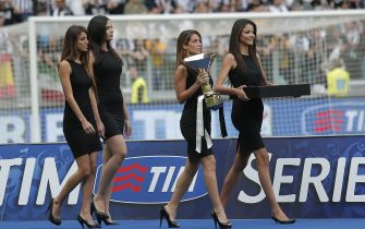 """Hostesses enter the field with the trophy and the medal before the trophy ceremony of the Italian Serie A after the last football game of the season Juventus vs Cagliari on May 18, 2014 at the Juventus Stadium in Turin. Juventus won their third consecutive """"scudetto"""". AFP PHOTO / MARCO BERTORELLO        (Photo credit should read MARCO BERTORELLO/AFP via Getty Images)"""