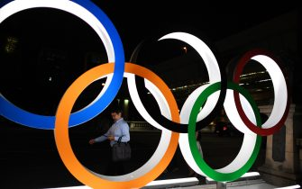 TOPSHOT - A man walks in front of the Olympic Rings displayed in the Tokyo's Nihonbashi district on July 24, 2019, as the city marks one year before the start of the Tokyo 2020 Olympic Games. - Tokyo entered the final leg of its marathon Olympic preparations, marking a year until the 2020 Games open with officials promising a high-tech but eco-friendly event. (Photo by CHARLY TRIBALLEAU / AFP)        (Photo credit should read CHARLY TRIBALLEAU/AFP via Getty Images)