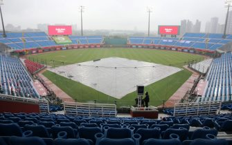 A masked broadcaster stands by at the Taoyuan Baseball stadium before the opening match for the Chinese Professional Baseball League (CPBL) in Taoyuan on April 11, 2020. - The match is called off due to the heavy rain. (Photo by Alex Lee / AFP) (Photo by ALEX LEE/AFP via Getty Images)