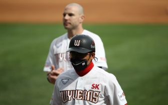 """INCHEON, SOUTH KOREA - MAY 05: (EDITORIAL USE ONLY) First base coach Cho Dong-hwa of SK Wyverns wears a mask during the Korean Baseball Organization (KBO) League opening game between SK Wyverns and Hanwha Eagles at the empty SK Happy Dream Ballpark on May 05, 2020 in Incheon, South Korea. The 2020 KBO season started after being delayed from the original March 28 Opening Day due to the coronavirus (COVID-19) outbreak. The KBO said its 10 clubs will be able to expand their rosters from 28 to 33 players in 54 games this season, up from the usual 26. Teams are scheduled to play 144 games this year. As they prepared for the new beginning, 10 teams managers said the season would not be happening without the hard work and dedication of frontline medical and health workers. South Korea is transiting this week to a quarantine scheme that allows citizens to return to their daily routines under eased guidelines. But health authorities are still wary of """"blind spots"""" in the fight against the virus cluster infections and imported cases. According to the Korea Center for Disease Control and Prevention, 3 new cases were reported. The total number of infections in the nation tallies at 10,804. (Photo by Chung Sung-Jun/Getty Images)"""
