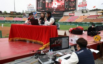 """INCHEON, SOUTH KOREA - MAY 05: (EDITORIAL USE ONLY) SK Wyverns staffs broadcast during the Korean Baseball Organization (KBO) League opening game between SK Wyverns and Hanwha Eagles at the empty SK Happy Dream Ballpark on May 05, 2020 in Incheon, South Korea. The 2020 KBO season started after being delayed from the original March 28 Opening Day due to the coronavirus (COVID-19) outbreak. The KBO said its 10 clubs will be able to expand their rosters from 28 to 33 players in 54 games this season, up from the usual 26. Teams are scheduled to play 144 games this year. As they prepared for the new beginning, 10 teams managers said the season would not be happening without the hard work and dedication of frontline medical and health workers. South Korea is transiting this week to a quarantine scheme that allows citizens to return to their daily routines under eased guidelines. But health authorities are still wary of """"blind spots"""" in the fight against the virus cluster infections and imported cases. According to the Korea Center for Disease Control and Prevention, 3 new cases were reported. The total number of infections in the nation tallies at 10,804. (Photo by Chung Sung-Jun/Getty Images)"""