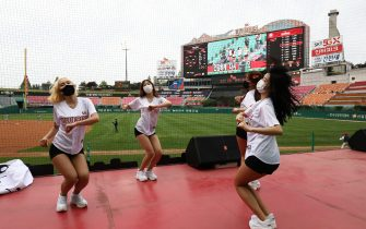 """INCHEON, SOUTH KOREA - MAY 05: (EDITORIAL USE ONLY) SK Wyverns cheerleaders at club's Happy Dream Ballpark during the Korean Baseball Organization (KBO) League opening game between SK Wyverns and Hanwha Eagles at the empty SK Happy Dream Ballpark on May 05, 2020 in Incheon, South Korea. The 2020 KBO season started after being delayed from the original March 28 Opening Day due to the coronavirus (COVID-19) outbreak. The KBO said its 10 clubs will be able to expand their rosters from 28 to 33 players in 54 games this season, up from the usual 26. Teams are scheduled to play 144 games this year. As they prepared for the new beginning, 10 teams managers said the season would not be happening without the hard work and dedication of frontline medical and health workers. South Korea is transiting this week to a quarantine scheme that allows citizens to return to their daily routines under eased guidelines. But health authorities are still wary of """"blind spots"""" in the fight against the virus cluster infections and imported cases. According to the Korea Center for Disease Control and Prevention, 3 new cases were reported. The total number of infections in the nation tallies at 10,804. (Photo by Chung Sung-Jun/Getty Images)"""