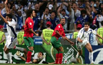 Greek striker Angelos Charisteas (R) celebrates in front of Portuguese players Ricardo Carvalho (2nd left) and Miguel (2nd right) after scoring the 1-0 lead during the Euro 2004 final between Portugal and Greece at Luz stadium in Lisbon on Sunday, 04 July 2004. ANSA/FILIPPO MONTEFORTE
