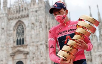 """Overall race winner Team Ineos rider Great Britain's Tao Geoghegan Hart wearing the leader's pink jersey holds the """"Never ending trophy"""" (Trofeo Senza Fine) as he celebrates on podium in front of the Duomo cathedral, after the the 21st and final stage of the Giro d'Italia 2020 cycling race, a 15,7-kilometer route between Cernusco sul Naviglio and Milano on October 25, 2020. (Photo by Luca Bettini / AFP)"""