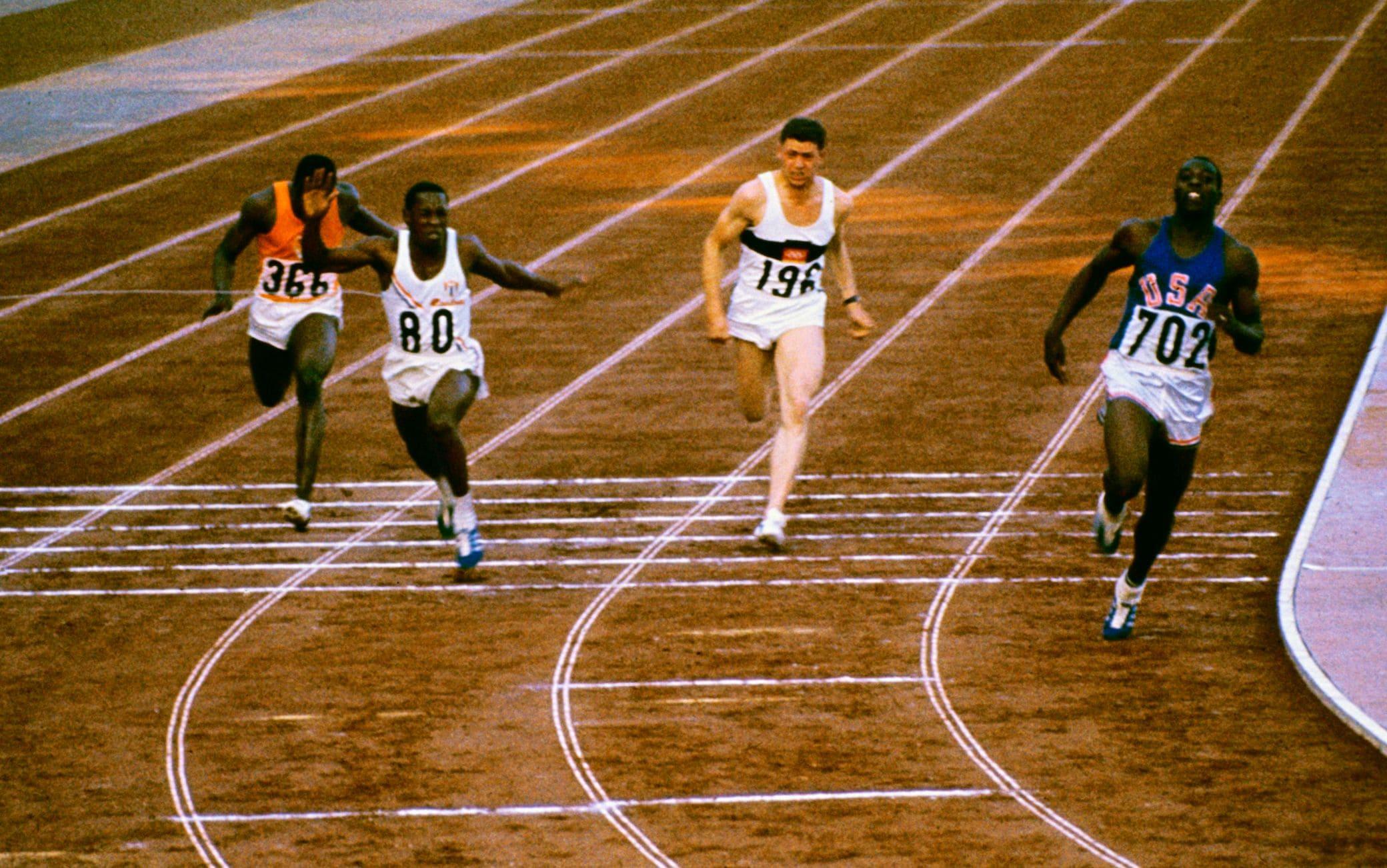 Bob Hayes taglia il traguardo nella finale dei 100 metri a Tokio, due scarpe solo apparentemente identiche: una chiodata, una da jogging