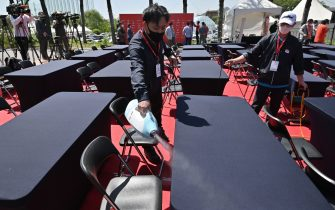 A staff sprays disinfectant on tables and seats before a press conference ahead of the 42nd KLPGA Championship at Lakewood Country Club in Yangju, northeast of Seoul, on May 13, 2020. - Leading professional golfers will return to competitive action for the first time in months after the coronavirus shutdown when three of the world's top 10 women tee off in South Korea on May 14. (Photo by Jung Yeon-je / AFP) (Photo by JUNG YEON-JE/AFP via Getty Images)
