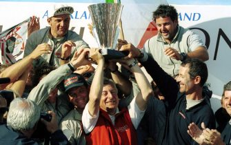 "AKL13 - 20000206 - AUCKLAND, NEW ZEALAND : Pertrizio Bertelli (""Mr Prada"" C-in red jacket) holds aloft the Louis Vuitton Cup with the help of the ""Luna Rossa"" crew at the cup presentation after Prada's win over ""AmericaOne"" on race day nine of the Louis Vuitton Cup finals in Auckland, New Zealand, 06 February 2000.  Prada won the start by one second and maintained their lead throughout the match, finishing 49 seconds ahead of AmericaOne and will go on to challenge for the America's Cup against Team New Zealand starting on the 19th of February. 