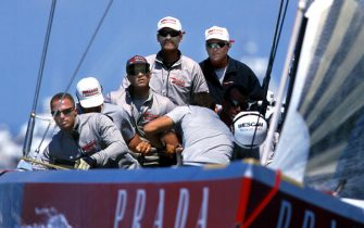 "The crew of Italian syndicate Prada on their yacht ""Luna Rossa"" with skipper Francesco de Angelis (centre, white cap, grey top) at the helm hoist their jib and go in search of wind while waiting for race control to lift the postponement on race day three of the America's Cup 2000 on the Hauraki Gulf, Auckland, 24 February 2000.  The race did not get a start and the Italians along with Team New Zealand will be back on the water 26 February hoping for better conditions. AFP PHOTO/DEAN TREML"