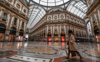 TOPSHOT - A general view shows a woman walk across the deserted Vittorio Emanuele II galleria shopping mall on March 10, 2020 in Milan. - Italy imposed unprecedented national restrictions on its 60 million people on March 10, 2020 to control the deadly coronavirus, as China signalled major progress in its own battle against the global epidemic. (Photo by Miguel MEDINA / AFP) (Photo by MIGUEL MEDINA/AFP via Getty Images)