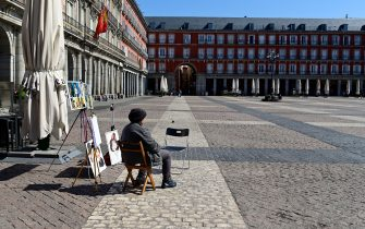 A street cartoonist waits for customers at the usually overcrowded Plaza Mayor in central Madrid on March 14, 2020 after regional authorities ordered all shops in the region be shuttered from today through March 26, save for those selling food, chemists and petrol stations, in order to slow the coronavirus spread. (Photo by JAVIER SORIANO / AFP) (Photo by JAVIER SORIANO/AFP via Getty Images)