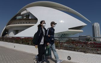 A couple wearing protective masks walk at the City of Arts and Sciences in Valencia on March 14, 2020 as Spain confirmed more than 1,500 new cases of coronavirus between Friday and Saturday raising its total to 5,753 cases, the second-highest number in Europe after Italy. - The country is expected to declare a state of alert to try to mobilise resources to combat the virus, which has so far killed 136 people in Spain. (Photo by JOSE JORDAN / AFP) (Photo by JOSE JORDAN/AFP via Getty Images)