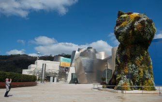 """A woman takes a picture of US artist Jeff Koons' installation """"Puppy"""" outside the usually overcrowded Guggenheim Bilbao Museum in the Spanish Basque city of Bilbao on March 14, 2020 as Spain confirmed more than 1,500 new cases of coronavirus between Friday and Saturday raising its total to 5,753 cases, the second-highest number in Europe after Italy. - The country is expected to declare a state of alert to try to mobilise resources to combat the virus, which has so far killed 136 people in Spain. (Photo by ANDER GILLENEA / AFP) / RESTRICTED TO EDITORIAL USE - MANDATORY MENTION OF THE ARTIST UPON PUBLICATION - TO ILLUSTRATE THE EVENT AS SPECIFIED IN THE CAPTION (Photo by ANDER GILLENEA/AFP via Getty Images)"""