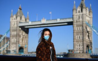 LONDON, ENGLAND - MARCH 22:  A member of the public poses for a photo in front of Tower Bridge whilst wearing a protective mask on March 22, 2020 in London, England. Coronavirus (COVID-19) has spread to at least 188 countries, claiming over 13,000 lives and infecting more than 300,000 people. There have now been 5,018 diagnosed cases in the UK and 233 deaths. (Photo by Alex Davidson/Getty Images)