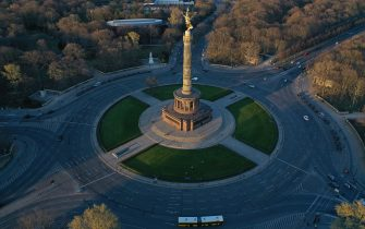 BERLIN, GERMANY - MARCH 23: (EDITOR'S NOTE: Photo taken with a drone.) In this aerial view the traffic circle at the Victory Column , which at rush hour is usually crowded with cars, stands nearly empty during the coronavirus crisis on March 23, 2020 in Berlin, Germany. The coronavirus and the disease it causes, COVID-19, are having a fundamental impact on society, government and the economy in Germany. Public life has been restricted to the essentials in an effort by authorities to slow the spread of infections. Hospitals are scrambling to increase their testing and care capacity. An economic recession seems likely as economic activity is slowed and many businesses are temporarily closed. Schools, daycare centers and universities remain shuttered. And government, both federal and state, seek to mobilize resources and find adequate policies to confront the virus and mitigate its impact. (Photo by Sean Gallup/Getty Images)