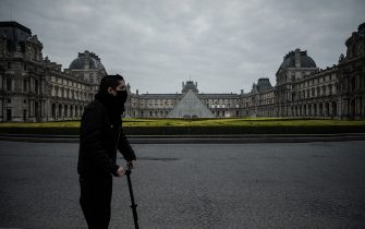 A man wearing a protective mask ride an eletric scooter in front of the Louvre palace in Paris, on March 18, 2020,  as a strict lockdown came into in effect in France to stop the spread of COVID-19, caused by the novel coronavirus. - A strict lockdown requiring most people in France to remain at home came into effect at midday on March 17, 2020, prohibiting all but essential outings in a bid to curb the coronavirus spread. The government has said tens of thousands of police will be patrolling streets and issuing fines of 135 euros ($150) for people without a written declaration justifying their reasons for being out (Photo by Philippe LOPEZ / AFP) (Photo by PHILIPPE LOPEZ/AFP via Getty Images)