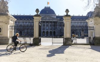 BRUSSELS, BELGIUM - MARCH 23: A man rides his bicycle in front of the Royal Palace of Brussels (Palais Royal de Bruxelles - Koninklijk Paleis van Brussel) on March 23, 2020 in Brussels, Belgium. Belgium government announced more measures asking all citizens to stay home and non-essential shops to close doors. 37 people have died in Belgium from Coronavirus disease 2019 (COVID-19 - SARS-CoV-2), with 2275 confirmed patients. (Photo by Thierry Monasse/Getty Images)