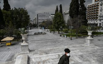 TOPSHOT - A man wearing a protective face mask walks at empty Athens' empty Syntagma square on March 23, 2020 as the country struggles to control the spread of the COVID-19, the novel coronavirus. (Photo by Aris Messinis / AFP) (Photo by ARIS MESSINIS/AFP via Getty Images)