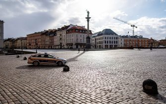 TOPSHOT - Municipal guard drives on the unusually empty Castle Square (Plac Zamkowy) in the old City of Warsaw, on March 14, 2020. - Polish government urged citizens to stay at home for a few weeks to limit the spread of the novel coronavirus. (Photo by Wojtek RADWANSKI / AFP) (Photo by WOJTEK RADWANSKI/AFP via Getty Images)