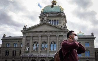 A tourist wearing a mask is seen in front of the Swiss House of Parliament on March 13, 2020, in Bern ahead of the announcement by Swiss government of new preventive measures against the spread of the COVID-19 caused by the novel coronavirus. (Photo by Fabrice COFFRINI / AFP) (Photo by FABRICE COFFRINI/AFP via Getty Images)