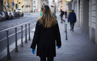 MILAN, ITALY - MARCH 24: A woman wears a face mask as Milan continues the lockdown of it's citizens in an attempt to limit the spread of the coronavirus outbreak on March 24, 2020 in Milan, Italy. The Italian government continues to enforce the nationwide lockdown measures to control the spread of COVID-19. As a result of new measures, Italy has seen the number of daily fatalities come down from a world record 793 on Saturday to 651 on Sunday and 601 on Monday. (Photo by Lorenzo Palizzolo/Getty Images)