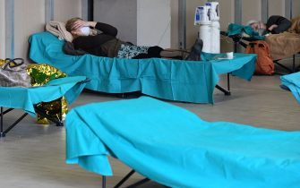 Patients lie in bed at a temporary emergency structure set up outside the accident and emergency department, where any new arrivals presenting suspect new coronavirus symptoms will be tested, at the Brescia hospital, Lombardy, on March 13, 2020. (Photo by Miguel MEDINA / AFP) (Photo by MIGUEL MEDINA/AFP via Getty Images)