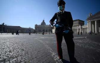 TOPSHOT - An armed Carabinieri police officer, wearing a face mask, patrols a closed and deserted St. Peter's Square in the Vatican on March 19, 2020 during the lockdown within the new coronavirus pandemic. (Photo by Filippo MONTEFORTE / AFP) (Photo by FILIPPO MONTEFORTE/AFP via Getty Images)