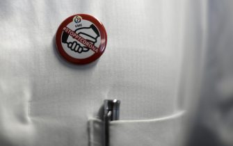 "A doctor wears a button reading ""Stop Corona"" and showing an icon requesting not to shake hands in order to minimize the risk of infection at the isolation ward of the Uniklinikum Essen university hospital in Essen, western Germany, on March 9, 2020. - The number of coronavirus cases in Germany has passed 1,000, official data from the Robert Koch Institute disease control centre showed. (Photo by INA FASSBENDER / AFP) (Photo by INA FASSBENDER/AFP via Getty Images)"