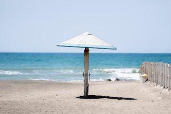 ROME, ITALY - MAY 10: An umbrella is seen on an empty and closed beach in the seaside town of Ostia during 'phase two' of measures to tackle the Coronavirus (Covid-19) pandemic, on May 10, 2020 in Rome, Italy. Italy was the first country to impose a nationwide lockdown to stem the transmission of the Coronavirus (Covid-19), and its restaurants, theaters and many other businesses remain closed. (Photo by Antonio Masiello/Getty Images)