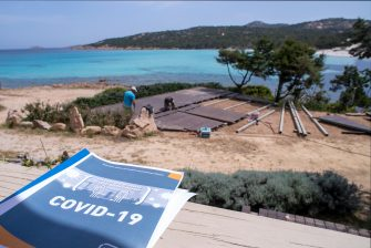 PORTO CERVO, ITALY - MAY 10: A tour operator begins to prepare the tables of the bar still closed to the public in front of a beach respecting the rules imposed by the Italian government, during 'phase two' of measures to tackle the Coronavirus (Covid-19) pandemic, on May 10, 2020 in Rome, Italy. Italy was the first country to impose a nationwide lockdown to stem the transmission of the Coronavirus (Covid-19), and its restaurants, theaters and many other businesses remain closed. (Photo by Emanuele Perrone/Getty Images)