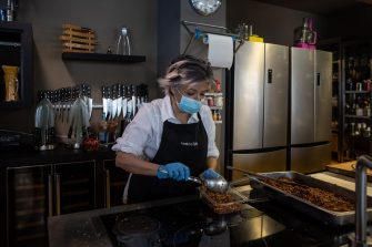 MILAN, ITALY - MAY 06: A woman, wearing protective gloves and a face mask, prepare meals to take away inside 'Teatro7 lab' cooking school, located in the Isola district on May 06, 2020 in Milan, Italy. Italy was the first country to impose a nationwide lockdown to stem the transmission of the Coronavirus (Covid-19), and its restaurants, theaters and many other businesses remain closed. (Photo by Emanuele Cremaschi/Getty Images)