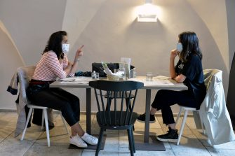 BOLZANO, ITALY - MAY 11: Two women wear face masks at a restaurant table on May 11, 2020 in Bolzano, Italy. The Bolzano province started the reopening of some businesses one week earlier than the rest of Italy, arising many controversies. (Photo by Alessio Coser/Getty Images)
