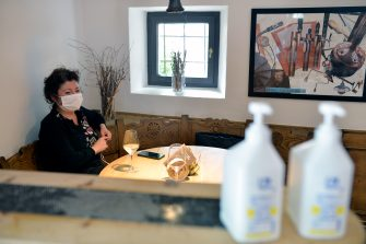 BOLZANO, ITALY - MAY 11: A woman wearing a face mask sits at a restaurant table on May 11, 2020 in Bolzano, Italy. The Bolzano province started the reopening of some businesses one week earlier than the rest of Italy, arising many controversies. (Photo by Alessio Coser/Getty Images)