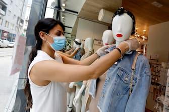 La proprietaria di un negozio di abbigliamento riallestisce la vetrina in vista delle riaperture del 18 maggio durante la fase 2 dell'emergenza Coronavirus a Milano, 14 maggio 2020.ANSA/Mourad Balti Touati