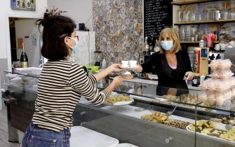 A girl wears a protective face mask as buys some coffees in a bar of Milan, Italy, 05 May 2020. Takeaway food and drink are now available in restaurants and bars with the start of the Phase 2 of the Covid-19 emergency.  ANSA/Mourad Balti Touati