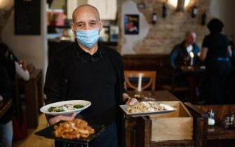 epa08424734 A waiter of the Italian restaurant 'Pepe Nero' wears a face mask as he he carries plates in Berlin, Germany, 15 May 2020. From Friday, 15 May 2020, gastronomic businesses are allowed again to host guests, with 1.5 meters distance to be kept, between seats. Restaurants and cafes had to close their businesses for a long time, due to the pandemic crisis of the SARS-CoV-2 coronavirus which causes the Covid-19 disease.  EPA/CLEMENS BILAN