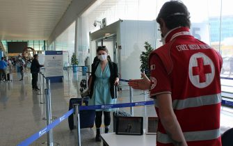 """An aiport employee wears a """"Smart-Helmet"""" portable thermoscanner to screen passengers and staff for the coronavirus COVID-19 disease at Terminal 3 in Rome Leonardo Da Vinci airport from different destinations, after the reopening of regional borders amid an easing of restrictions during Phase 2 of the coronavirus emergency, in Fiumicino, Italy, 03 June 2020. Several countries around the world have started to ease COVID-19 lock-down restrictions in an effort to restart their economies and help people in their daily routines after the outbreak of coronavirus pandemic. al Terminal 3.ANSA/TELENEWS"""