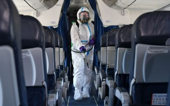 An employee wearing personal protective equipment disinfects a planes cabin at the Boryspil International Airport outside Kiev on June 13, 2020, while the airport prepares to restart regular international flights in line with an easing of coronavirus restrictions in Ukraine. (Photo by Genya SAVILOV / AFP) (Photo by GENYA SAVILOV/AFP via Getty Images)