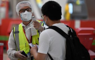 An employee in full protective gear checks the temperature of a passenger arriving to check in for his flight bound for Beijing at the Barajas airport in Madrid on June 20, 2020, a day before the country's state of emergency ends following a national lockdown to stop the spread of the novel coronavirus. - With Spain's epidemic now well under control, the government has been cautiously easing out of its mid-March lockdown with travel restrictions soon to be lifted as well. (Photo by PIERRE-PHILIPPE MARCOU / AFP) (Photo by PIERRE-PHILIPPE MARCOU/AFP via Getty Images)