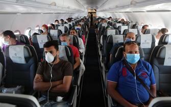 epa08498690 Passengers wearing protective face masks travel on a plane at Sharm el-Sheikh International Airport, Egypt, 20 June 2020.  EPA/KHALED ELFIQI