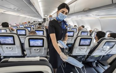 """Egyptian cabin crew distribute masks on a domestic flight at Cairo International Airport on June 18, 2020 during the Covid-19 pandemic crisis. - Egypt will reopen its airports on July 1 and begin welcoming to beach resorts tourists kept away by the coronavirus pandemic, the government announced. Flights will resume """"between Egypt and countries which have reopened their airspace"""", said Aviation Minister Mohamed Manar during a news conference in Cairo. (Photo by Khaled DESOUKI / AFP) (Photo by KHALED DESOUKI/AFP via Getty Images)"""