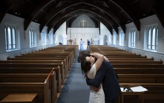 ARLINGTON, VIRGINIA - APRIL 18:  Newly married Tyler and Caryn Suiters embrace following their marriage ceremony performed by Rev. Andrew Merrow in an otherwise empty St. Mary's Episcopal Church April 18, 2020 in Arlington, Virginia. Rev. Merrow and his wife Cameron Merrow were the only other attendees at the ceremony due to social distancing guidelines implemented in the wake of the COVID-19 pandemic. (Photo by Win McNamee/Getty Images)