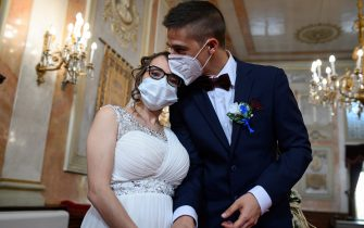 epa08469981 Groom Iker (R) and bride Aranzazu (L) wear face masks during their civil wedding at the town hall of Alcala de Henares, Madrid, Spain, 06 June 2020. The nuptial ceremony was one of the first held there since the the state of emergency was implemented in March throughout Spain due to the pandemic COVID-19 disease caused by the SARS-CoV-2 coronavirus. The current regulations for marriages stipulate a maximum number of 10 guests and the mandatory use of protective face masks.  EPA/FERNANDO VILLAR