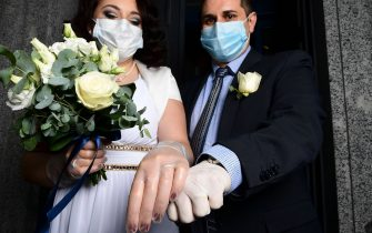 Newly-wed Italians Ester Concilio (L) and Rafaele Carbonelli wearing face masks show wedding rings under the protective gloves following the ceremony at the Briosco's town hall, about 45 km ( 28 miles) north of Milan, on May 11, 2020 during the country's lockdown aimed at curbing the spread of the COVID-19 infection, caused by the novel coronavirus. (Photo by Miguel MEDINA / AFP) (Photo by MIGUEL MEDINA/AFP via Getty Images)