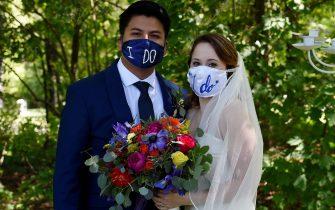 Newly married couple Rachel and Sebastian Vasquez wearing face masks, poses for pictures on May 9, 2020, after a ceremony at the Glencliff Manor in Rustburg, Virginia. - The Glencliff Manor officiates free, socially distanced ceremonies for couples left with no wedding plans during the coronavirus pandemic. Only ten people are allowed at each hour-long ceremony. (Photo by Olivier DOULIERY / AFP)