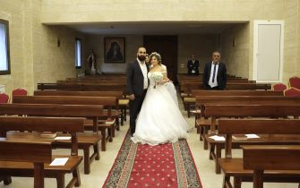 Maya Khadra and Rakan Ghossein (R) pose for a picture during their wedding at the church Our Lady Of Assistance in the village of Shemlan south of Beirut on April 25, 2020. - For months Maya and Rakan had looked forward to their dream wedding in the Vatican -- but the coronavirus pandemic forced them to settle for a tiny church ceremony in Lebanon. (Photo by ANWAR AMRO / AFP) (Photo by ANWAR AMRO/AFP via Getty Images)