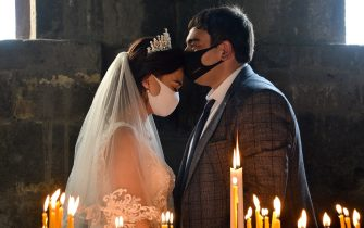 TOPSHOT - A bride and a bridegroom wearing protective face masks exchange kisses during a wedding ceremony in a church in the Saghmosavan village outside Yerevan on June 14, 2020, as the country tries to curb the spread of the COVID-19, the disease caused by the novel coronavirus. (Photo by Karen MINASYAN / AFP) (Photo by KAREN MINASYAN/AFP via Getty Images)