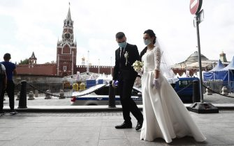 epa08469135 Newly-weds in their wedding garb wear protective face masks as they walk on the Red Square during the annual Red Square Book Fair in Moscow, Russia, 06 June 2020. The Red Square Book Fair is the first public event allowed by the authorities since the outbreak of the ongoing pandemic of the COVID-19 disease caused by the SARS-CoV-2 coronavirus. The literary festival runs from 06 to 08 June.  EPA/MAXIM SHIPENKOV