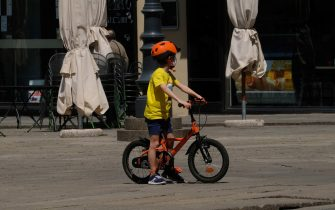A child on a bicycle at Loggia square on the first day of the Phase two during the coronavirus emergency in Brescia, northern Italy, 04 May 2020. The Italian government announced a gradual lifting of the lockdown restrictions that were implemented to stem the widespread of the Sars-Cov-2 coronavirus causing the Covid-19 disease. Fom 04 May on, the country's population will be again allowed to move around their region, among others. More restrictions are set to be lifted on 18 May and 01 June 2020.ANSA/ FILIPPO VENEZIA