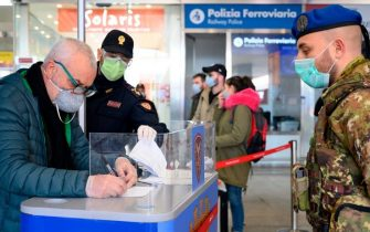 A soldier (R) and a police officer (Rear L) wearing a respiratory mask check a man filling an access form as part of control measures against the spread of the new COVID-19 coronavirus, at the Termini railway station in Rome on March 10, 2020. - Italy imposed unprecedented national restrictions on its 60 million people on March 10, 2020 to control the deadly coronavirus, as China signalled major progress in its own battle against the global epidemic. (Photo by Tiziana FABI / AFP) (Photo by TIZIANA FABI/AFP via Getty Images)