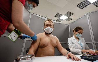 Zenit supporter (C) receives a dose of the Sputnik V vaccine against COVID-19 at newly opened vaccination center operating at the stadium ahead of the Russian Premier League match between FC Zenit Saint Petersburg and FC Akhmat Grozny on March 13, 2021 at Gazprom Arena in Saint Petersburg, Russia. (Photo by Mike Kireev/NurPhoto via Getty Images)
